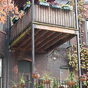 Boston's South End neighborhood is known for its rows of restored brick townhouses and trendy restaurants. Unusual porches on back side of building with potted plants.