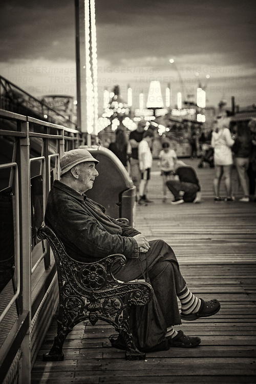 An eldelry male figure sitting on a bench on Brigton pier tapping his foot to the loud music while young people scream on the rides