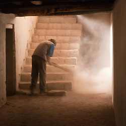 In the dark halls of the Leh Palace a worker cleans the dust from the stairs.