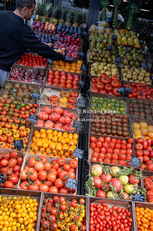 An employee of local grocer 'Bora & Sons' tends to the display of fruit and veg outside the retailer's business on Lordship Lane in East Dulwich, on 25th October 2021, in London, England.