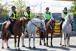 London, UK. 4 September, 2019. Metropolitan Police officers on horseback stand in one of the two main access roads to ExCel London during protests on the third day of a week-long carnival of resistance against DSEI, the world's largest arms fair. The third day's protests were organised by the Campaign for Nuclear Disarmament (CND) and Trident Ploughshares.