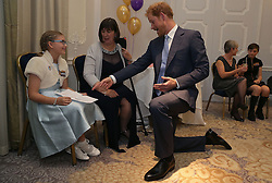 Prince Harry (centre) reacts as he meets Good Morning Britain Inspirational Young Hero Award Winner Jessica Davis (left) and her mother Paula (second left), as he attends the WellChild Awards in London. The awards recognise the courage of seriously ill children, their families and carers.
