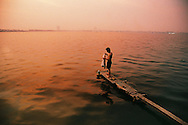 Young vietnamese man standing on a tiny boarding in west lake by sunset. Hanoi, Vietnam, Asia