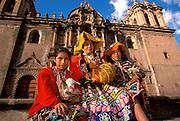 PERU, HIGHLANDS, CUZCO Plaza de Armas; girls in trad.dress