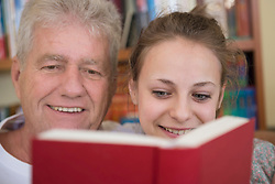Grandfather and granddaughter reading book on couch in living room, smiling