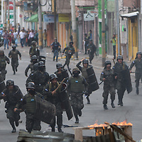 Many human rights observers have talked about the increasing militarisation of Honduras, with military figures being given government positions as well as military being given increased powers and visibility. Military and police have also recently been given wage increases.<br /> <br /> Here members of the Honduran Navy charge a barricade raised by protestors against the inauguration of Juan Orlando Hernandez in Tegucigalpa. It seems strange using the Navy for riot duties, knowing that the nearest sea is around 150km from Tegucigalpa. Reportedly, every member of every armed force in the country has been brought out onto the street to contain protests.