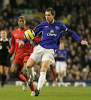 Photo: Dave Howarth.<br /> Everton v Liverpool. The Barclays Premiership. 28/12/2005. Everton's David Weir beats Liverpool's Djibril Cisse to the ball