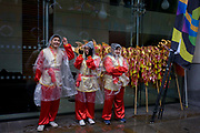 Chinese dragon dancers before the Lord Mayor's Show in the City of London, the capital's ancient financial district founded by the Romans in the 1st Century. This is the pageant's 800th birthday and the 250 year-old horse-drawn guided State Coach will be pulled through the medieval streets with the newly-elected Mayor along with 7,000 others. This first took place in 1215 making it the oldest and longest civil procession in the world which survived both Bubonic plague and the Blitz.