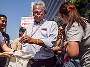 21 JANUARY 2014 - BANGKOK, THAILAND: SUTHEP THAUGSUBAN, collects cash from supporters during a march down Thanon Naradhiwas Rajanagarindra in the financial district of Bangkok. Suthep, the leader of the anti-government protests and the People's Democratic Reform Committee (PDRC), the umbrella organization of the protests, led a march through the financial district of Bangkok Tuesday. Shutdown Bangkok has entered its second week with no resolution in sight. Suthep is still demanding the caretaker government of Prime Minister Yingluck Shinawatra resign and the PM says she won't resign and intends to go ahead with the election.     PHOTO BY JACK KURTZ