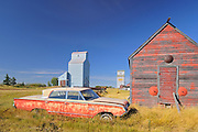 Old car, grain elevator and sheds<br /> Darcy<br /> Saskatchewan<br /> Canada