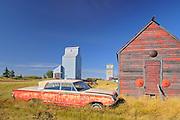 Old car, grain elevator and sheds<br /> Darcy<br /> Saskatchewan<br /> Canada