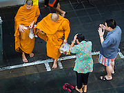 30 DECEMBER 2015 - BANGKOK, THAILAND: Thais make merit by presenting monks with food in Bang Chak Market. The market is supposed to close permanently on Dec 31, 2015. The Bang Chak Market serves the community around Sois 91-97 on Sukhumvit Road in the Bangkok suburbs. About half of the market has been torn down. Bangkok city authorities put up notices in late November that the market would be closed by January 1, 2016 and redevelopment would start shortly after that. Market vendors said condominiums are being built on the land.           PHOTO BY JACK KURTZ