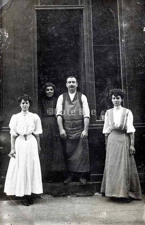 shop owner with workers posing in door opening France 1910s