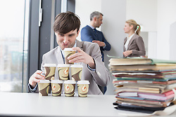 Businessman building tower with coffee cups while businesspeople in background