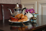 a breakfast tray with Freshly baked croissants with a pot of hot coffee