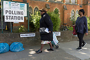 On the morning of the European Elections in the UK, two local women walk, one carrying her polling card, past the Polling Station at the Baptist Church in East Dulwich. Barnabas Parish Hall in Dulwich Village, on 23rd May 2019, in south London, England UK.