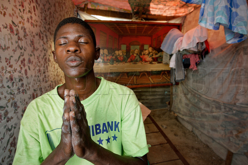 Michele Elisnor, 23, prays after hanging inside his tent a depiction of Jesus Christ's Last Supper. Elisnor says he cannot sleep at night so he hung the painting in the hopes of warding off voodoo spirits that keep him awake at night. Haiti's only golf course is home to tens of thousands survivors at the Petion-Ville Club golf course on March 3. 2010...