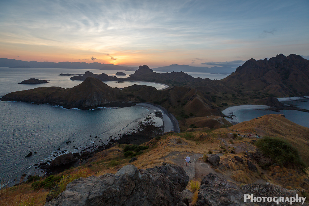 Woman hikes a trail along the ridge tops of the Komodo islands as sun sets behind distant mountians