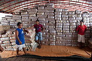 men selling rice in a stock pile of packets on a boat on the Xingu river in the Amazonian state of Para