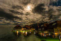 Overwater bungalows at night in the moonlight, Hilton Moorea Lagoon Resort, island of Moorea, French Polynesia.
