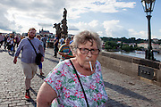 An elderly woman with a cigarette walking on Charles Bridge. The Charles Bridge (Czech: Karlův most) is a famous historic bridge that crosses the Vltava river in Prague, Czech Republic and is probably the Nr.1 tourists magnet in the city.
