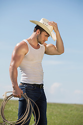 hot muscular cowboy with a lasso on a ranch