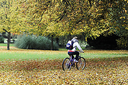 © Licensed to London News Pictures. 26/10/2012.A young girl cycles across autumnal leaves on the ground making a blanket of colour in The Priory Gardens in Orpington, Kent..Photo credit : Grant Falvey/LNP