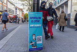 Licensed to London News Pictures. 19/05/2021. London, UK. Members of the public walk past Covid-19 information signs in Hounslow, south-west London. Downing Street has warned that the Indian variant has spread to 86 local authorities with clusters in the north-west and London including Hounslow, Croydon and Hillingdon. However, Prime Minister Boris Johnson revealed in the House of Commons today that vaccines are effective against all variants including the Indian one. Photo credit: Alex Lentati/LNP