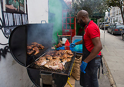 © Licensed to London News Pictures. 30/08/2020. London, UK. A man cooks jerk chicken outside a property in Notting Hill, West London, on the first day of the 2020 Notting Hill Carnival, which is being held virtually this year due to COVID-19 restrictions. Members of the public have been warned against congregating in the Notting Hill Area to celebrate the event. Photo credit: Ben Cawthra/LNP