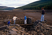 Locals walk over the exposed stone walls of the once-thriving village of Ashopton that now lies at the bottom of Ladybower reservoir, Derbyshire, England. Remains of the village were revealed during the drought of 1989 the levels of water dropped from the country's reservoirs as rainfall failed in the heatwave while demand peaked in the cities such as Sheffield. The villages of Derwent & Ashopton were submerged when the valley was flooded, between 1943 & 1945, amid much controversy. Derwent church tower was left standing at first, but demolished in 1947 for safety reasons. The remains of the buildings are still visible when the water is very low, as it was in 1989.