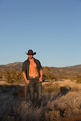 cowboy with an open shirt leaning on a fence post