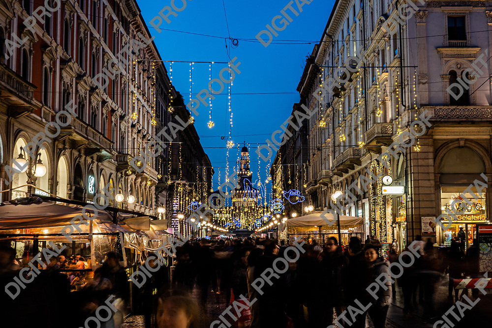 Blurred people walking along Via Dante decorated with glowing garlands hanging above in evening during Christmas vacation in Milan Italy