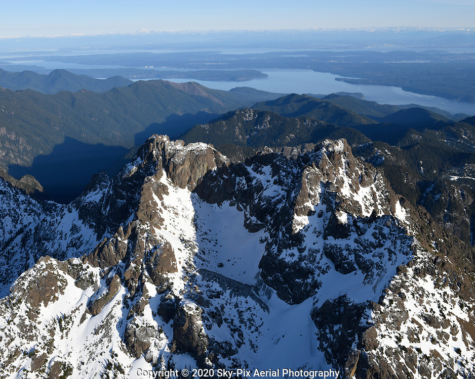 Aerial view of the peaks of The Brothers, taken from the west side of the mountain, looking east toward the Cascade Range, with Hood Canal, the Toandos Peninsula, and the Kitsap Peninsula in the background.