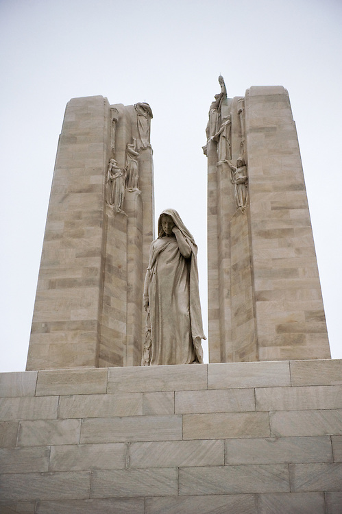 """The weeping woman or better known as """"Mother Canada mourning her dead"""" in front of the twin white pylons of the Canadian National Vimy Memorial dedicated to the memory of Canadian Expeditionary Force members killed in World War one. The monument is situated at a 100 hectare preserved battlefield with wartime tunnels, trenches, craters and unexploded munitions. The memorial designed by Walter Seymour Allward opened in 1936."""