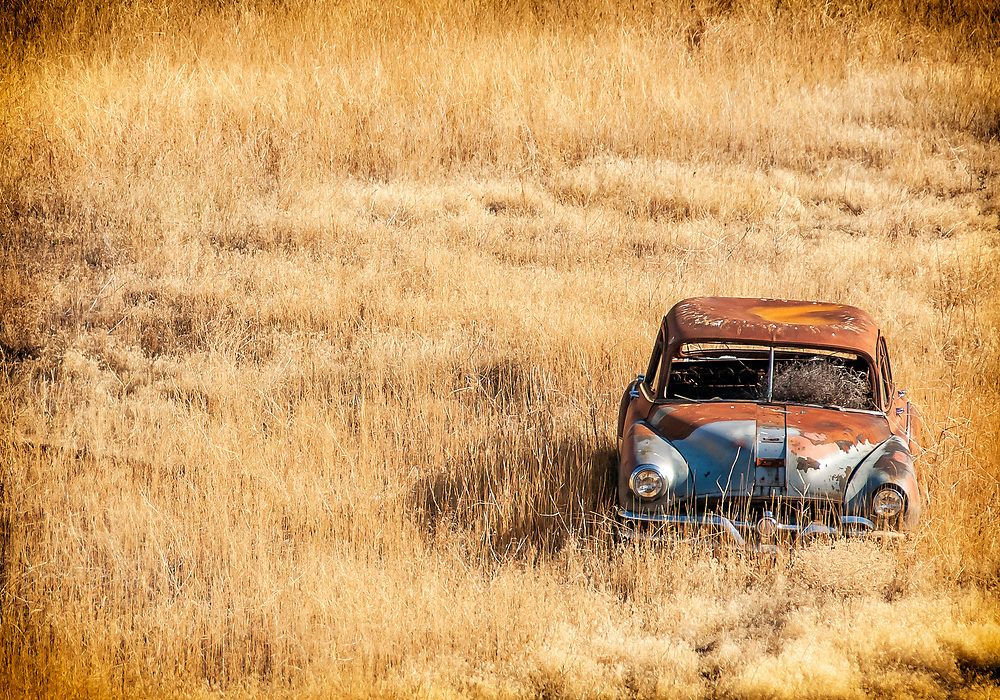 Abadoned old car rusting away in a field.