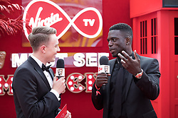 EDITORIAL USE ONLY<br /> Marcel Somerville (right) spills the beans to Virgin TV's red-carpet host Roman Kemp in Virgin TV's Must-See Moment Lounge at the Virgin TV British Academy Television Awards.