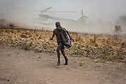 A boy moves away as a United Nations World Food Programme (WFP) helicopter lands in Rubkuai village, Unity State, northern South Sudan, February 2017.
