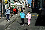 Two children (9 years old, 5 years old) walking a cobbled street. Zagreb, Croatia