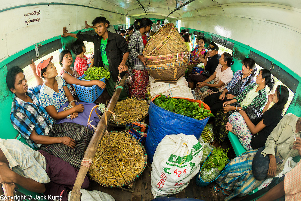15 JUNE 2013 - YANGON, MYANMAR:  Market vendors ride the Yangon Circular Train to a market outside of Yangon. The Yangon Circular Railway is the local commuter rail network that serves the Yangon metropolitan area. Operated by Myanmar Railways, the 45.9-kilometre (28.5 mi) 39-station loop system connects satellite towns and suburban areas to the city. The railway has about 200 coaches, runs 20 times and sells 100,000 to 150,000 tickets daily. The loop, which takes about three hours to complete, is a popular for tourists to see a cross section of life in Yangon. The trains from 3:45 am to 10:15 pm daily. The cost of a ticket for a distance of 15 miles is ten kyats (~nine US cents), and that for over 15 miles is twenty kyats (~18 US cents). Foreigners pay 1 USD (Kyat not accepted), regardless of the length of the journey.     PHOTO BY JACK KURTZ