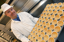 Hospital kitchen Production Manager in bakery section holding tray of pastry cases,