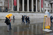 A Yoda busker and umbrellas beneath the columned architecture of the National Gallery in Trafalgar Square, Westminster, on 9th April 2019, in London, England.