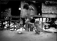 Girl jumping rope while boys are distracted by a visitor, the ever present waters of Tonle Sap visible beneath posts of mobile houses in Chong Kneas, Cambodia.