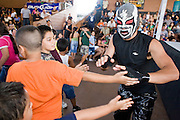 "July 13, 2008 -- PHOENIX, AZ: Luchador (wrestler) Pequeno Dragon (Little Dragon) greets his fans before a Lucha Libre show at El Gran Mercado in Phoenix. He is ""tecnico"" or good guy in the Lucha show. Lucha Libre is Mexican style wrestling. There are heros (Tecnicos) and villians (Rudos). The masks are popular as children's gifts and tourist mementos. As the size of the Mexican community in the Phoenix area has grown, attendance at the Lucha Libre shows has increased. Lucha Libre differs from American style entertainment wrestling in several ways, but principally the wrestlers are more acrobatic and rely less on body slams than American wrestling. The shows, which used to be held only periodically, are now held every week at El Gran Mercado, a flea market and swap meet that caters mostly to the Mexican community in Phoenix.   Photo by Jack Kurtz / ZUMA Press"