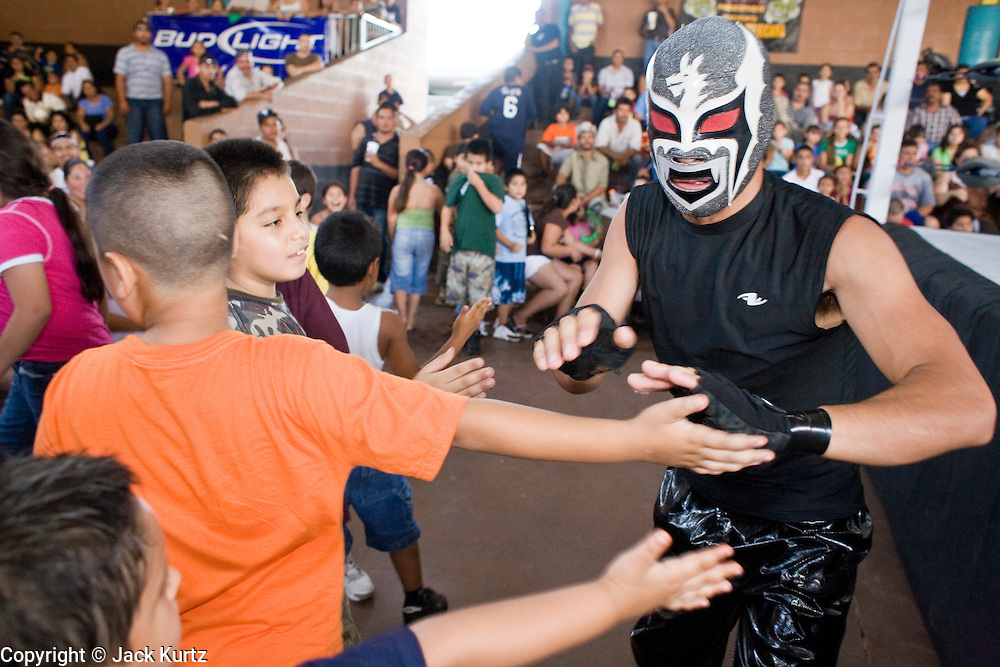 """July 13, 2008 -- PHOENIX, AZ: Luchador (wrestler) Pequeno Dragon (Little Dragon) greets his fans before a Lucha Libre show at El Gran Mercado in Phoenix. He is """"tecnico"""" or good guy in the Lucha show. Lucha Libre is Mexican style wrestling. There are heros (Tecnicos) and villians (Rudos). The masks are popular as children's gifts and tourist mementos. As the size of the Mexican community in the Phoenix area has grown, attendance at the Lucha Libre shows has increased. Lucha Libre differs from American style entertainment wrestling in several ways, but principally the wrestlers are more acrobatic and rely less on body slams than American wrestling. The shows, which used to be held only periodically, are now held every week at El Gran Mercado, a flea market and swap meet that caters mostly to the Mexican community in Phoenix.   Photo by Jack Kurtz / ZUMA Press"""