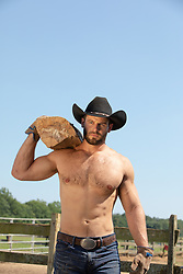 cowboy without a shirt working on a ranch