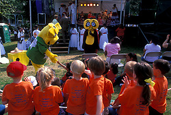 Stock photo of a costumed mascot meeting a crowd of young children at the International Festival in downtown Houston Texas