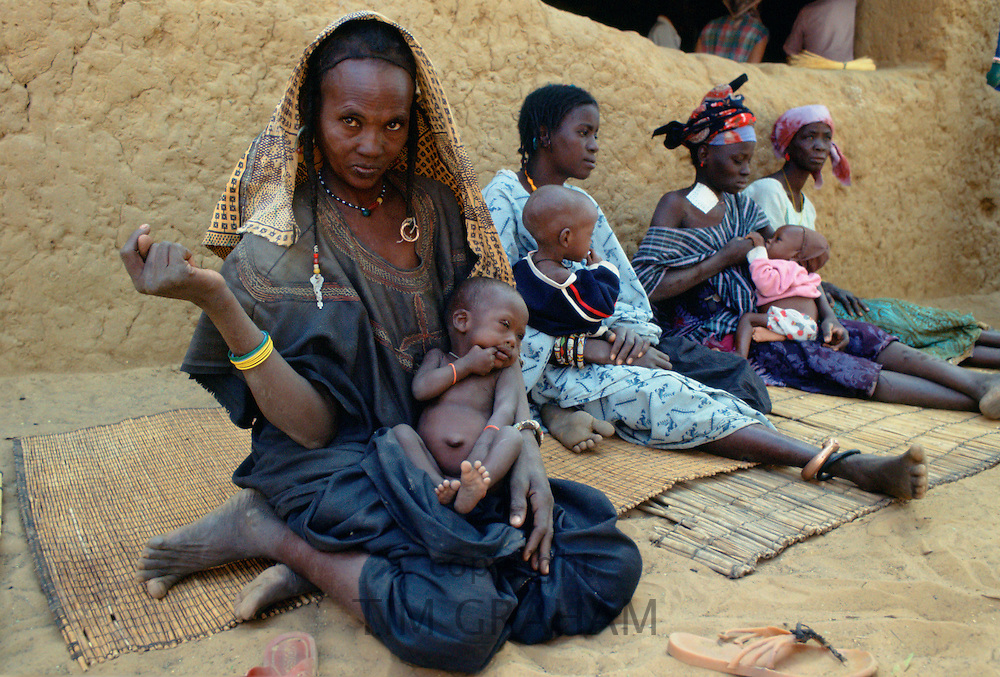 Mothers and children sitting on mats while waiting at Gorom Gorom Hospital in Burkina Faso (formerly Upper Volta)
