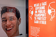 A model's face from the high street retailer, Primark alongside a government ad urging the public to wear a face covering on public transport, or face fines of up to £6,400, on 8th March 2021, in London, England.