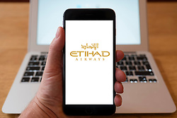 Using iPhone smartphone to display logo of Etihad airlines from Abu Dhabi, UAE