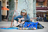 A young woman who had recently traveled around the world strums her guitar and sings while sitting near the Rotunda in Aix-en-Provence, France